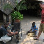 Erick Luchs (right) watches as a wheelchair is prepared for Lazarus Moyo (centre) who spent 20 years crawling due to his disability.