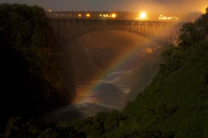 Moonbow appearing close to the Victoria Falls Bridge