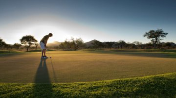 A golfer lining up a put as the sun goes down. (Image via Omeya Golf and Residential Oasis)
