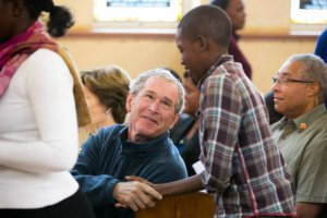 Former President George W. Bush meets a young Livingstone resident at the Mosi Oa Tunya Clinic
