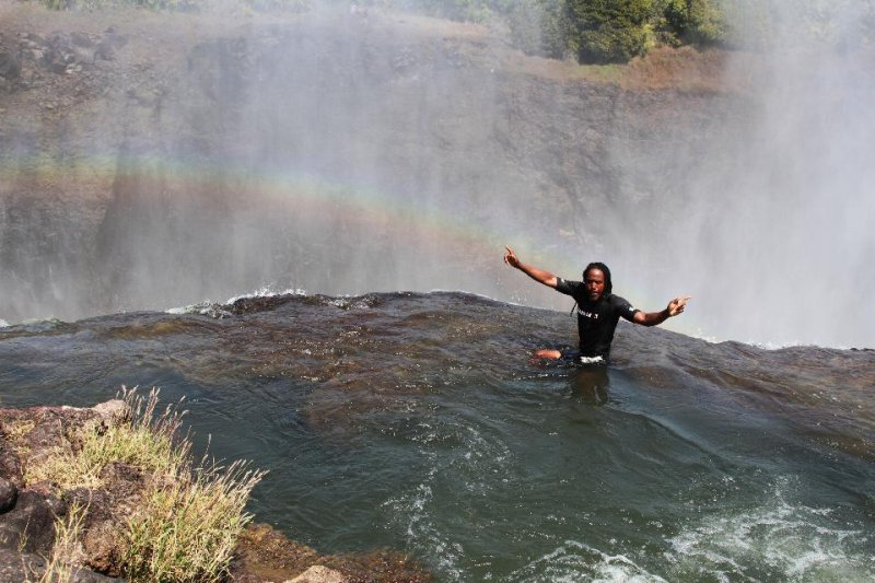 A local guide shows how to jump into the Devil's Pool at the top of the Victoria Falls at the border of Zimbabwe and Zambia.