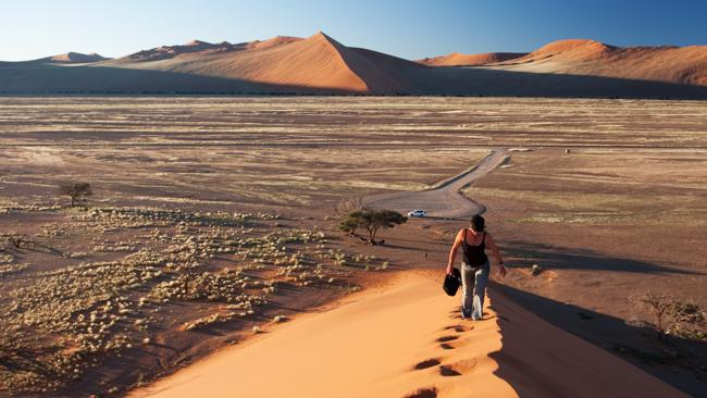 A woman walking up the ridge of sand dune in Namibia