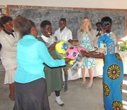 AWF's Lupani Conservation Primary School students and parents excitedly receive gifts of soccer balls and jump ropes from Chelsea Clinton of the Clinton Foundation.