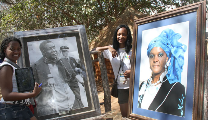 Danai Pawandiwa and Tapiwa Kupfuwa at the potraits of President Mugabe and First Lady Amai Grace at the Zimbabwe cultural centre