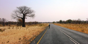 Isabel riding along the road through Botswana
