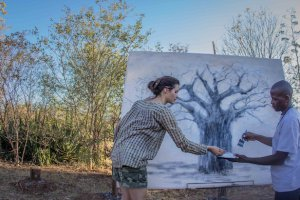 Acclaimed South African artist Nicola Taylor and Zambian forest hero (and ex charcoal burner) Lloyd Maanyina paint a tree using charcoal to signify the complex issues that charcoal burning poses in Zambia.