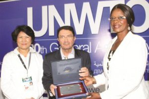 UNWTO secretary general Taleb Rifai (centre) presenting the Vettor Giusti tourism posters competition award scooped by Zambia, to Minister of Tourism and Arts Sylvia Masebo (right).