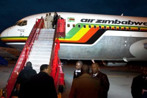 Zimbabwe President Robert Mugabe, top steps, center, in Denmark for a U.N. event. Air Zimbabwe, a national emblem, is making a slow turnaround.