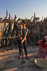 A visitor helps grind Mahangu. Mahangu is a delicious staple found in Namibia's north.