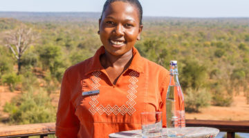 IMAGE CAPTION: Victoria Falls Safari Lodge waitress Kudakwashe Ruwuya serves water in a re- useable glass bottle, a major step towards the hospitality group's goal of going single-use plastic- free by 2021.